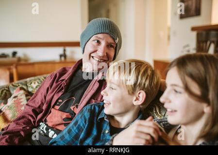 Vater und Kinder entspannen auf Sofa im Wohnzimmer Stockbild