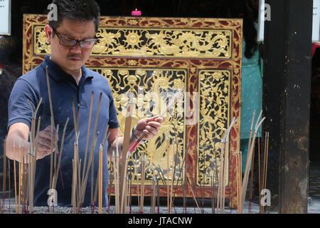 Ein chinesischer Mann, der betet und mit Weihrauch, Thian Hock Keng Tempel, Singapur, Südostasien, Asien Stockbild