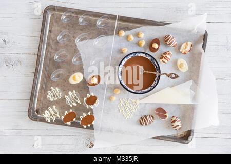 Hausgemachte Milch und weiße Schokolade Ostereier auf einem rustikalen Tisch. Stockbild
