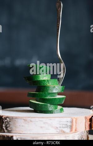 Gestapelt in Scheiben geschnittene Zucchini und Gabel auf rustikalen Schneidebrett Stockbild
