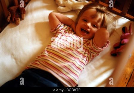 Foto des Kindes in Babys Kinderbett Lachen Lachen Lächeln verlegen Stockbild