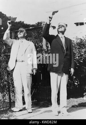Präsident Herbert Hoover und Lawrence Richey Beobachtung einer Sonnenfinsternis durch getöntes Glas. August Stockbild
