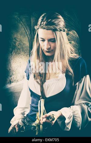 Mittelalterliche Frau, die einen Dolch hält Stockbild