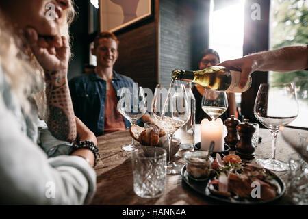Mann Hand strömenden Weißwein aus der Flasche in Gläser mit Freunden am Tisch sitzen. Gruppe von Stockbild