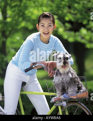 Frau auf einem Fahrrad mit ihrem Hund im Korb Stockbild
