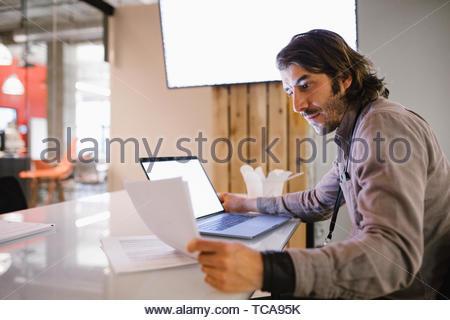 Konzentrierte Geschäftsmann spät am Laptop arbeiten in Konferenzraum Stockbild
