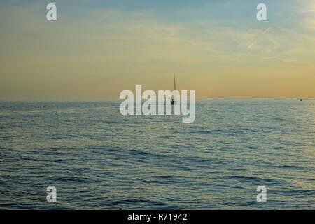 Einem Segelboot auf dem offenen Wasser im Abendlicht. Stockbild