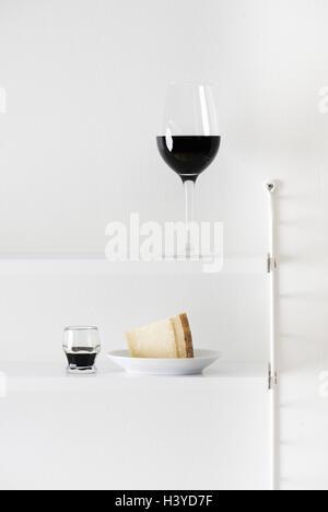 Rotwein, Parmesan und Balsamico-Essig im Bücherregal. Essen-Stilleben. Stockbild