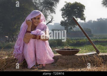 Lächelnd weibliche Betriebsinhaber oder Dorf Frau sitzt in der Nähe von Landwirtschaft Feld mit einem Spaten und Eisen Gold Pan durch Ihre Seite mit den Kopf bedeckt mit Sari. Stockbild