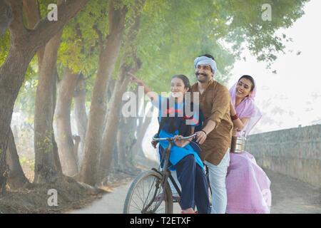 Happy ländlichen Paar zusammen mit ihrer Tochter reiten auf dem Fahrrad auf in das Dorf mit dem Mädchen auf den Finger. Stockbild