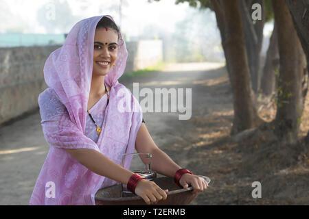Lächelnd ländliche Frau oder tageslohn Arbeiter in Saree tragen ein Bügeleisen Gold Pan in der Hand und einem Tiffin Box zu arbeiten. Stockbild