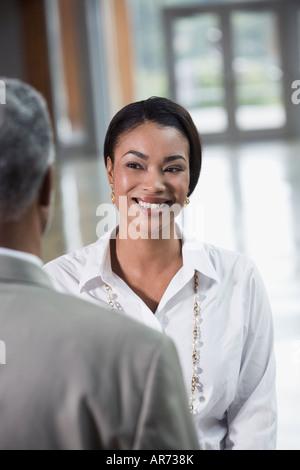 Afrikanische Geschäftsfrau lächelnd an Mitarbeiter Stockbild