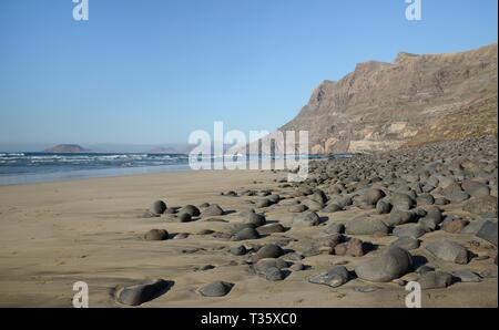 Famara Strand und Klippen mit im Hintergrund die Insel La Graciosa, Lanzarote, Kanarische Inseln, Februar. Stockbild