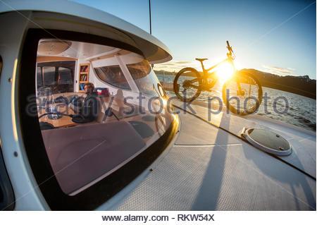 Man liest ein Buch in der Kabine eines Katamarans, als die Sonne hinter einem Mountainbike auf dem Deck Richtung Norden auf den Oslo Fjord. Stockbild