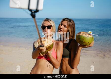 Zwei schöne junge Frauen im Bikini am Strand, im Gespräch Selbstbildnis mit Smartphone auf Selfie kleben. Stockbild