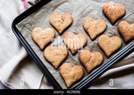 Hohen Winkel in der Nähe von frisch gebackenen Hart-förmige Cookies auf dem Backblech. Stockbild