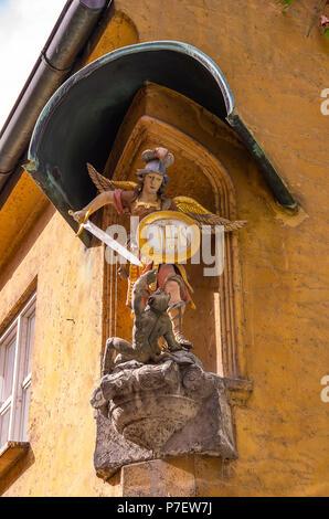 Fuggerei, Augsburg, Bayern, Deutschland - Darstellung des Erzengels Michael im Kampf gegen die Teufel an der Ecke eines Hauses. Stockbild