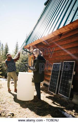 Paar Installation von Sonnenkollektoren und Regentonne auf Kabine Stockbild