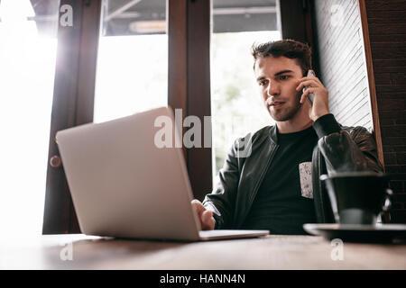 Innenaufnahme der junge Mann sitzt an einem Cafétisch mit Laptop und Handy telefonieren. Gut aussehend Kaukasischen Stockbild