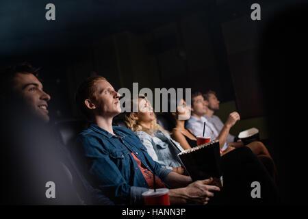 Junger Mann mit Freunden im Kinosaal Film. Gruppe von Menschen Film im Theater. Stockbild