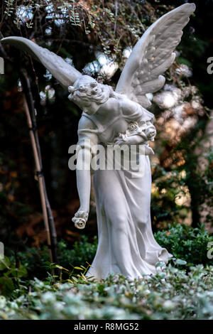 Statue eines Engels mit einem Korb voller Rosen als Teil einer Grabstein auf einem Grab Stockbild