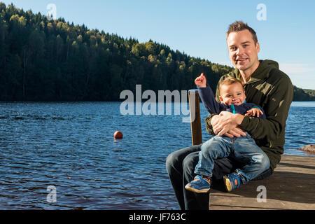 Vater und Sohn sitzen auf Steg See Stockbild