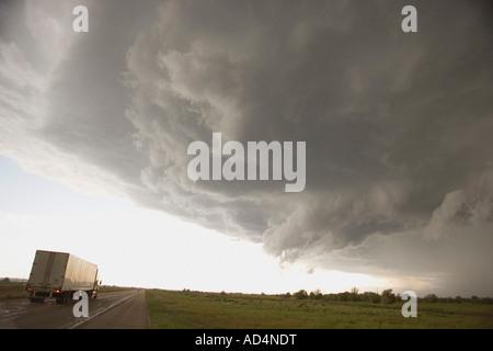 Gewitterwolken über eine ländliche Landschaft und einem Lastwagen auf der Autobahn Stockbild