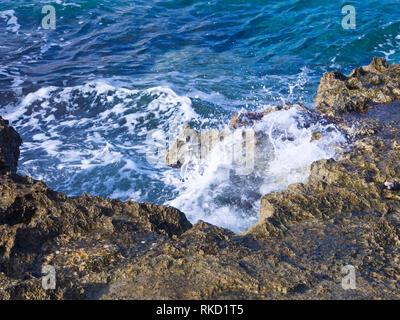 Blick entlang der Küste zu Fuß in St. Julians Malta, herbstliche Sonne und Mittelmeer blaue Meer macht es zu einem beliebten Ferienziel Stockbild
