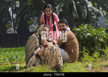 Glücklich und lächelnd ländlichen Familie sitzt in ihrer Landwirtschaft Feld. Stockbild