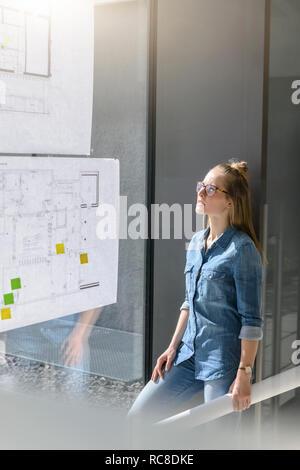 Frau betrachten Pläne auf Glas Wand Stockbild