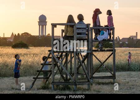 Kinder beobachten Sonnenuntergang am ehemaligen Flughafen Tempelhof, Berlin Stockbild
