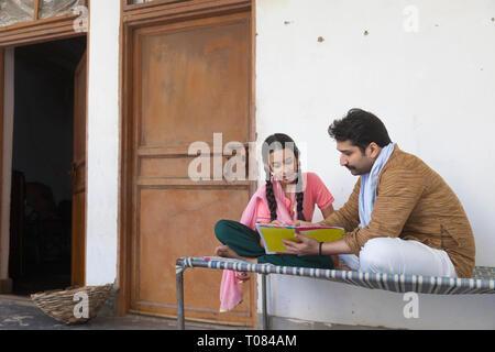 Dorf Mann mit seiner Tochter sitzt auf einem Kinderbett und ein Buch lesen. Stockbild