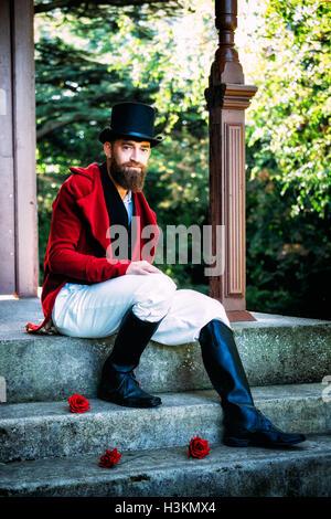 Regency Mann saß auf einer Stufe mit roten Rosen Stockbild