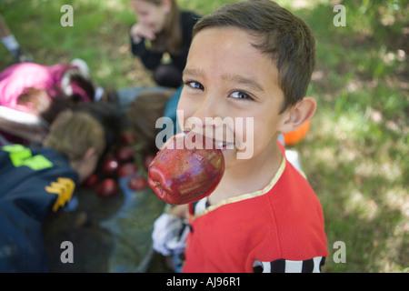 Kleiner Junge hält Apfel in den Mund, während andere Kinder für Äpfel im Hintergrund Schaukeln sind Stockbild