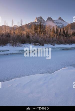 Winter Sonnenaufgang mit gefrorenen Bow River und drei Schwestern, Canmore, Alberta, kanadischen Rocky Mountains, Kanada, Nordamerika Stockbild