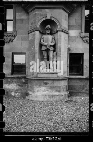 Statue eines Ritters, netherby Hall, Arthuret, Cumbria, c 1955 - c 1980. Eine detaillierte Ansicht der Statue eines gepanzerten Ritter stand mit seinen Händen ruht auf dem Knauf seines Schwertes, mit dem Visor von seinem Helm so hob sein Gesicht gesehen werden., in einem Runden-Nische an der Unterseite des ursprünglichen Turm aus dem 15. Jahrhundert der Halle geleitet. Netherby Halle war ursprünglich ein Turmhaus aus dem 15. Jahrhundert, mit Wänden 2 Meter dick, geglaubt, von der Römischen fort und wurde im Jahre 1639 für Sir Richard Graham erweitert. Weitere Ergänzungen des 18. Jahrhunderts, einschließlich der Garten vorne, die Reverend Robert Gr durchgeführt Stockbild