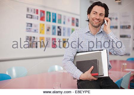 Lächelnde Geschäftsmann mit Laptop und Bücher im Gespräch mit Handy im Büro Stockbild