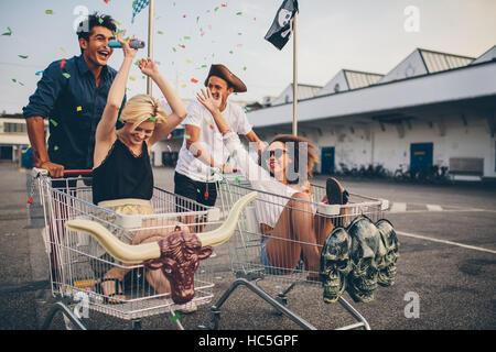 Multiethnische Jugendlichen racing mit Warenkorb. Junge Freunde, die Spaß an einem shopping Carts und Konfetti. Stockbild