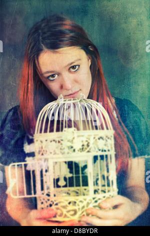 Junge weibliche Erwachsene halten eine leere Vogelkäfig Stockbild