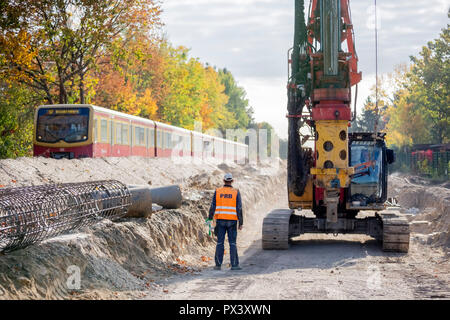 Berlin, Germany. 19th Oct, 2018. A construction worker is standing on the future route of the Dresdner Bahn in the section between the S-Bahn station Lichtenrade and the border Berlin-Brandenburg between a drill and a passing S-Bahn. Deutsche Bahn is pushing ahead with the expansion of the line. (to 'Railway is driving the construction of the Dresden railway' from 20.10.2018) Credit: Christoph Soeder/dpa/Alamy Live News Stockbild