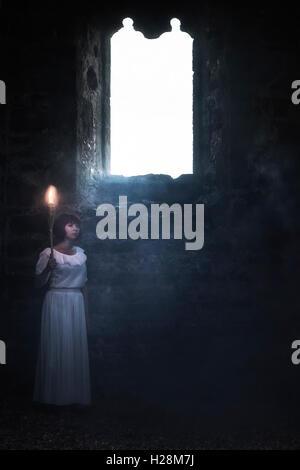 eine gespenstische Frau in einem weißen Kleid steht in einer alten Kirche mit einer Fackel Stockbild