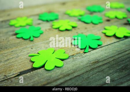 Schöne Nahaufnahmen der vielen Irischen shamrocks, fest Klee, in einer Reihe, daß Glück erinnern oder St. Patrick's Day mit Bokeh und hölzerne Tische als Hintergrund Stockbild