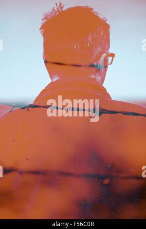 Doppelbelichtung eines Mannes und Stacheldraht Stockbild