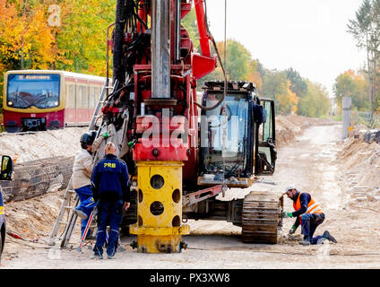 Berlin, Germany. 19th Oct, 2018. Construction workers are waiting for a drill on the future route of the Dresden Railway in the section between the Lichtenrade S-Bahn station and the Berlin-Brandenburg border, while an S-Bahn passes by. Deutsche Bahn is pushing ahead with the expansion of the line in the direction of Dresden and the BER in the south of Berlin. (to 'Railway is driving the construction of the Dresden railway' from 20.10.2018) Credit: Christoph Soeder/dpa/Alamy Live News Stockbild