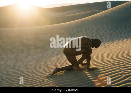 Nackte Frau kauerte in der Wüste Stockbild