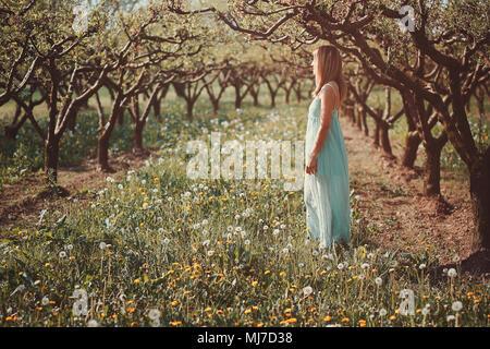 Frau genießen Sonne in einem Obstgarten. Ruhe und Harmonie Stockbild
