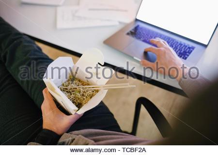 Mann spät am Laptop arbeiten, Essen, Essen nehmen Stockbild
