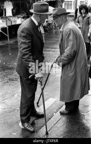 Markt Tag Landwirte Chat Dorf Leben der 1970er Jahre Uk Großbritannien tragen-Walking-Stöcke und Hüte Stockbild
