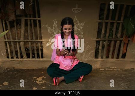 Glückliche junge Mädchen in ihrem Dorf ländliche Haus sitzt mit einem Mobiltelefon. Stockbild