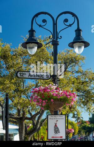 Straßenschilder, Blumen und Laternen entlang trendy 3rd Street Einkaufsviertel, Naples, Florida, USA Stockbild